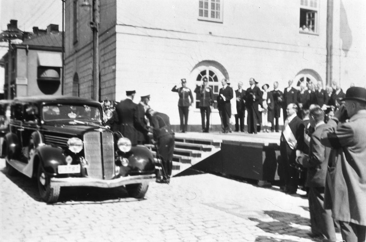 Kung Gustaf V och prins Wilhelm använder i bil till festligheterna i Arboga. Här ska firas Riksdagens 500-årsjubileum. Två män i uniform gör honnör. En scen är uppbyggd på Stora torget, intill Rådhuset. (Arbogautställningen pågår samtidigt och kungen ska hinna besöka den också).