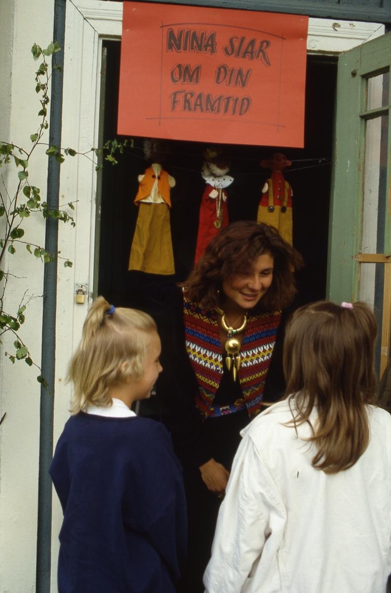 I lusthuset, i Olof Ahllöfs park, står Nina och siar om framtiden. Några barn är på besök.