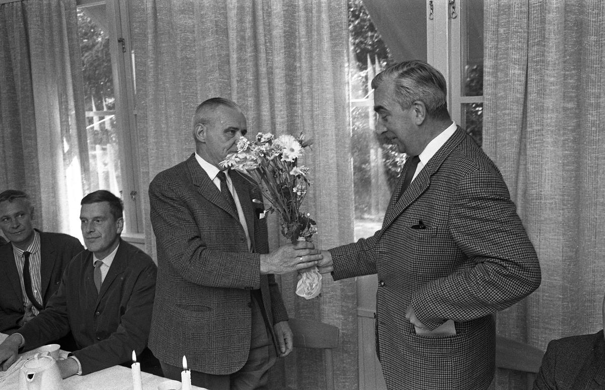 Alf Hedlund, maskinmästare, går i pension från Centrala Verkstaden Arboga. Anders Högfeldt uppvaktar med blommor. Bakom Alf sitter ingenjör Knut Hall.  Män i kostym. Kaffekoppar och vit duk.