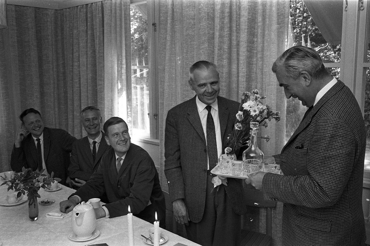 Alf Hedlund, maskinmästare, går i pension från Centrala Verkstaden Arboga. Han uppvaktas av Anders Högfeldt med blommor och present.  Från vänster: Henry Fredriksson, Sigvard Brohmé och Knut Hall.  Glada män i kostym. Vit duk med kaffekoppar. Blombuketter, karaff med glas i present.