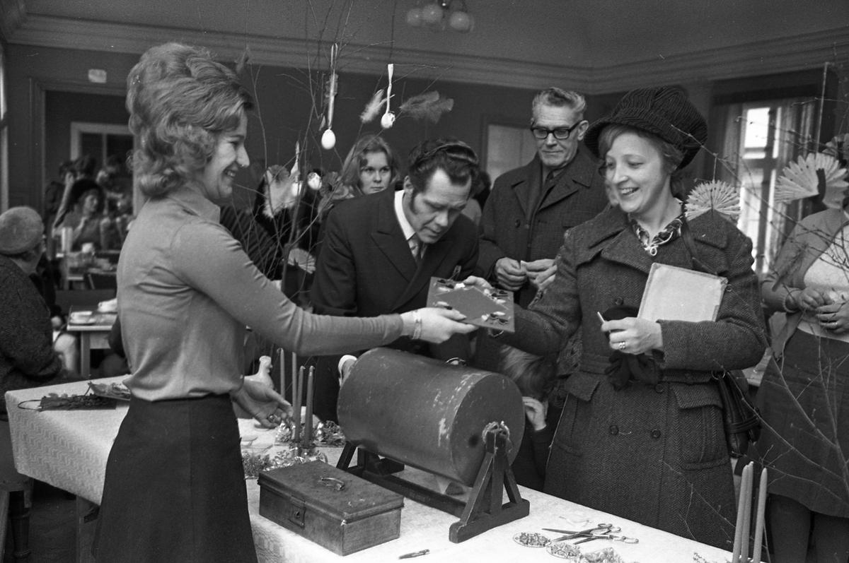 Försäljning hos Arbetareföreningen. Människor köper lotter och dricker kaffe. Påskris.