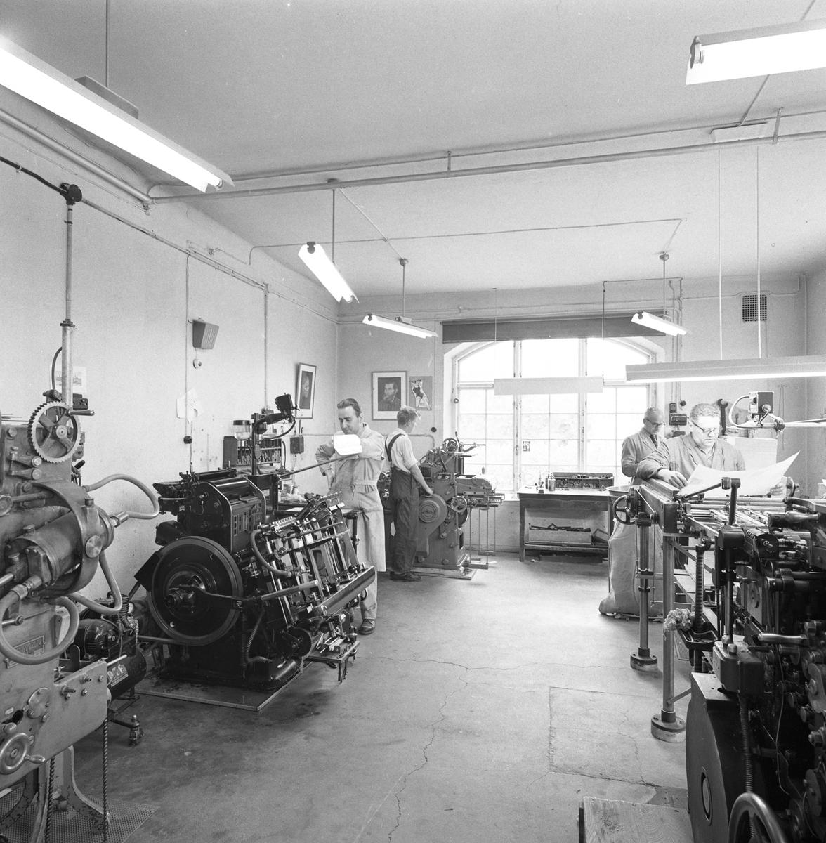 Arboga Boktryckeri, interiörbild från 1950-talet. Fyra män, iklädda arbetskläder, står vid var sin maskin. Ett stort fönster släpper in mycket ljus. Nils Munther är mannen närmast kameran, till höger.