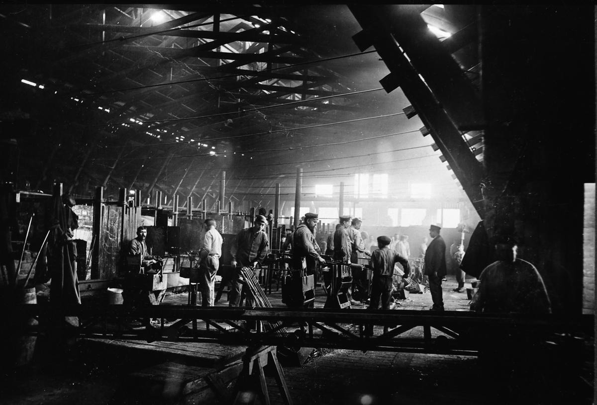 """Arboga Glasbruk, interiör, reprofoto. Män och pojkar arbetar i lokalen.  Uppgifterna om vilket år glasbruket etablerades varierar; 1867, 1870 och 1874 är exempel.  Bolagsordningen, för Arboga Glasbruks AB, stadfästes 1875. Bruket anlades nära hamnen och järnvägen. Buteljer fraktades till Stockholm med lastångaren """"Trögelin"""". På glasbruket tillverkades ca 400 olika sorters flaskor, olika storlekar inräknade. Glasbruket lades ner 1928.  Läs om Arboga Glasbruk i Hembygdsföreningen Arboga Minnes årsböcker 1982 och 2011."""
