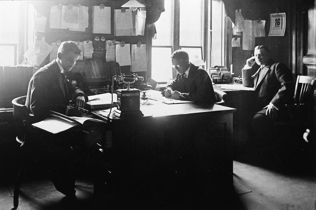 """Arboga Glasbruk, reprofoto. Tre välklädda herrar sitter i ett gemensamt kontor. Två sitter på var sin sida av ett brett skrivbord. Den tredje har ett eget skrivbord i hörnet. En man bär glasögon, en annan röker. På väggen, mellan fönstren. är diverse papper (beställningsordrar?) uppsatta. En skomakarlampa hänger över det breda skrivbordet. På skrivbordet står en telefon med vev.  Uppgifterna om vilket år glasbruket etablerades varierar; 1867, 1870 och 1874 är exempel.  Bolagsordningen, för Arboga Glasbruks AB, stadfästes 1875. Bruket anlades nära hamnen och järnvägen. Buteljer fraktades till Stockholm med lastångaren """"Trögelin"""". På glasbruket tillverkades ca 400 olika sorters flaskor, olika storlekar inräknade. Glasbruket lades ner 1928.  Läs om Arboga Glasbruk i Hembygdsföreningen Arboga Minnes årsböcker 1982 och 2011."""