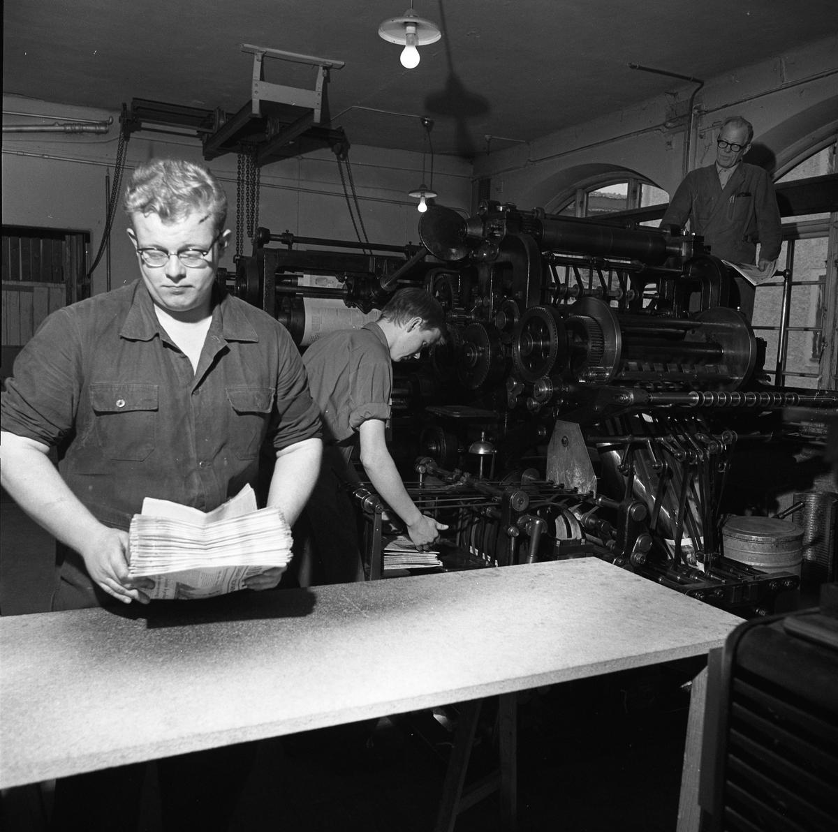 Arboga Tidning, personal och interiör. Tre personer i arbete vid tryckpressen. Männen hanterar hopsatta tidningar.