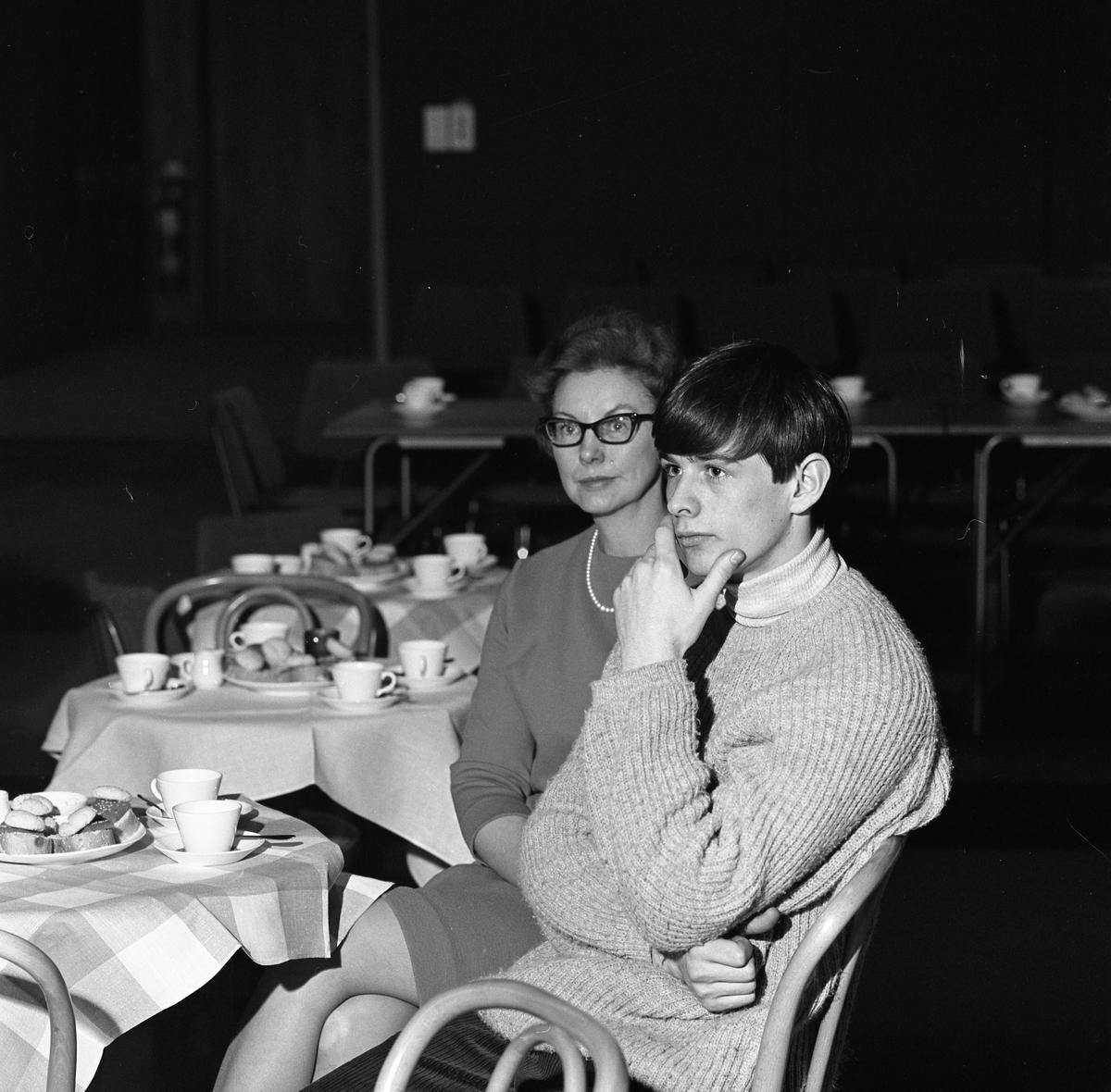 Arbogabor deltar vid radioprogrammet Frukostklubben, ett underhållningsprogram som sänds på lördagsmorgnar. En kvinna och en ung man sitter vid ett runt bord och dricker kaffe.