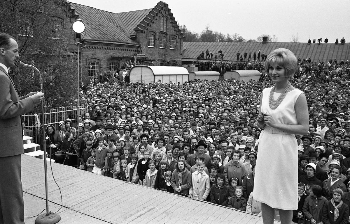 Barnens Dag firas. En stor publik är samlad nedanför scenen. Konfrencier, för modevisningen, är TV-kändisen Olle Björklund. Kvinnan är oidentifierad. Ett par flickor, närmast scenen, har på sig Barnens-Dags-blomman. Till vänster i bild ses Arboga Margarinfabrik