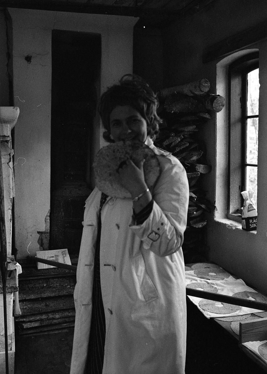 Brödbakning vid Jäders bruk. En kvinna i skyddsrock smakar på färskt knäckebröd. Vid fönstret ligger bröd och svalnar.