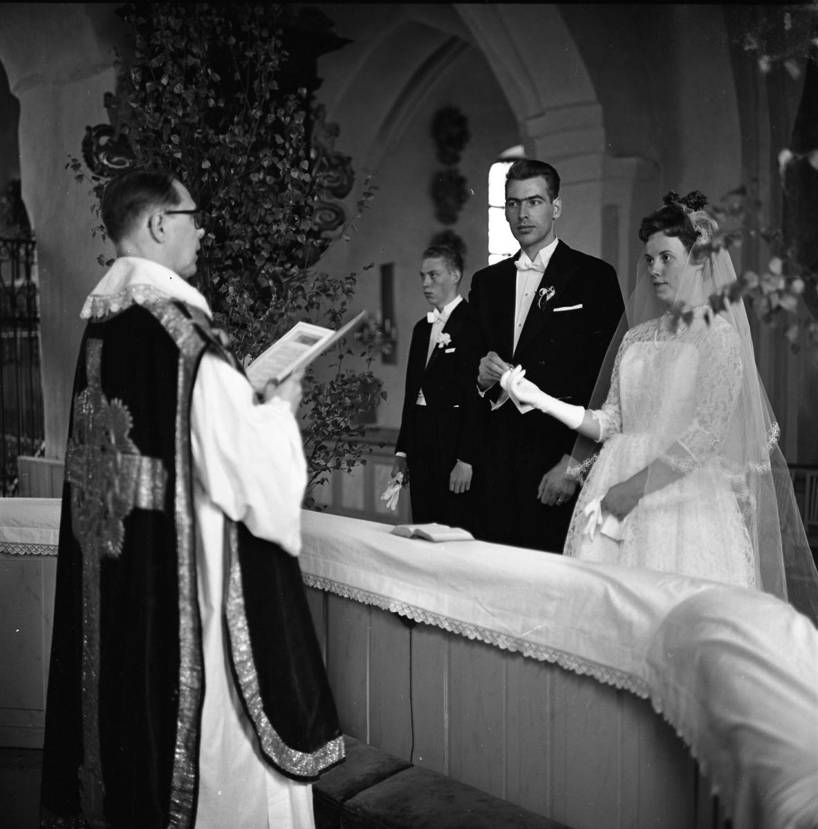 Ernst Hansson förrättar vigsel i Säterbo kyrka. Herr Olsson och fröken Tallqvist avlägger sina löften. Bruden har tagit av handsken på den hand där vigselringen ska vara. Kyrkan är dekorerad med björkar.