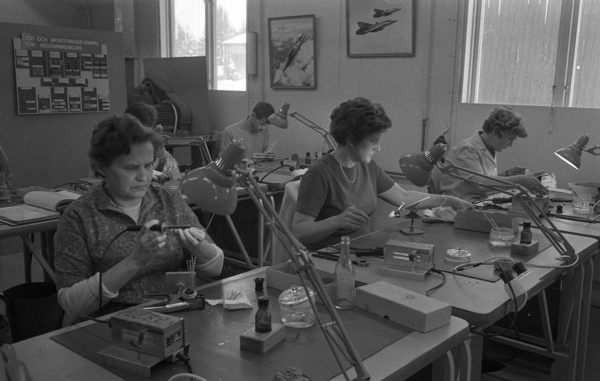 Kurs i lödning på CVA. Tre kvinnor sitter vid var sitt arbetsbord. Bakom dem sitter fler elever. Alla har verktyg och arbetslampa på bordet. Centrala Verkstaden Arboga