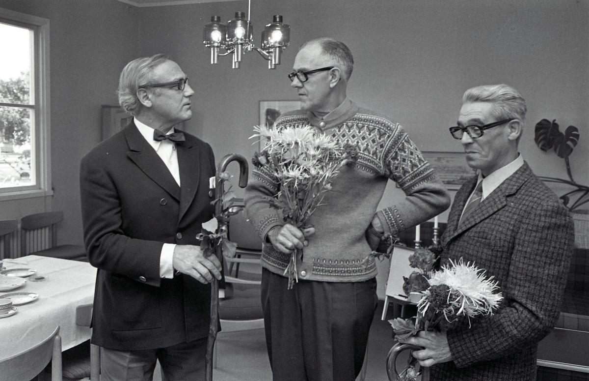 CVA-pensionärer Två män avtackas. Den ene är klädd i stickad tröja, den andre i kavaj. Båda har fått en bukett med krysantemum och nejlikor. Båda får också var sin promenadkäpp. I bakgrunden ses ett dukat kaffebord, en lampa hänger i taket. Centrala Verkstaden Arboga
