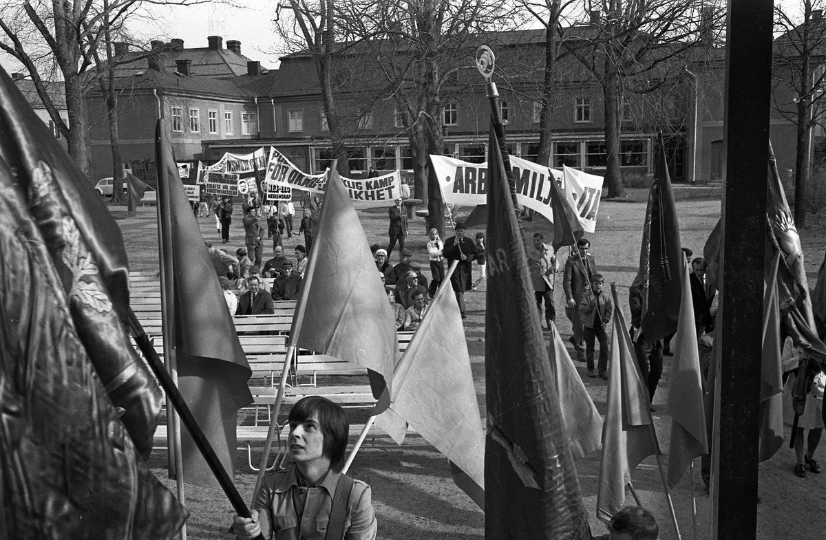 Demonstration på första maj. Demonstrationståget anländer till Olof Ahllöfs park. Människor bär plakat och banderoller. Byggnaden i bakgrunden är Stadskällaren.