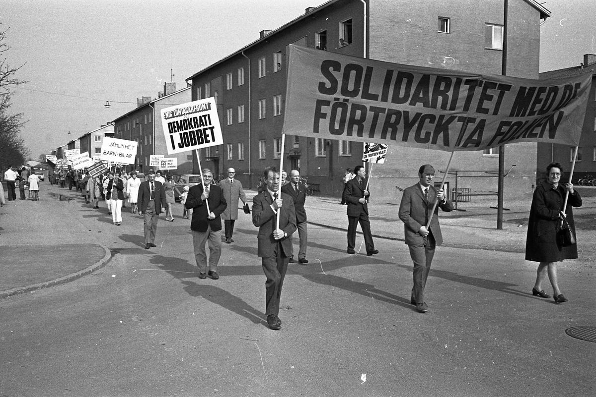 """Demonstrationståg på första maj. Nils Brodin bär ett plakat om """"Demokrati på jobbet"""". Bakom honom går Karl Pettersson."""