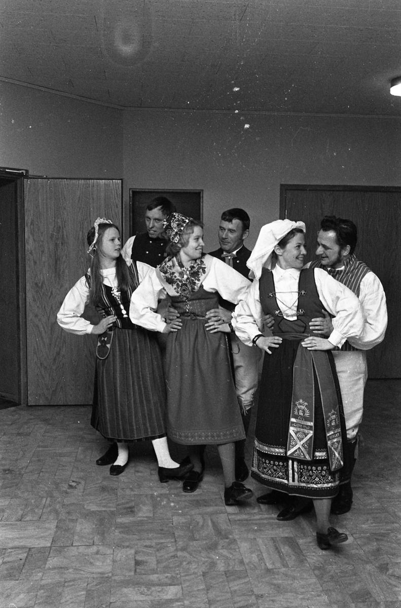 Tre par folkdansare poserar i foajén på Folkets Hus/Medborgarhuset. Samtliga bär folkdräkt.