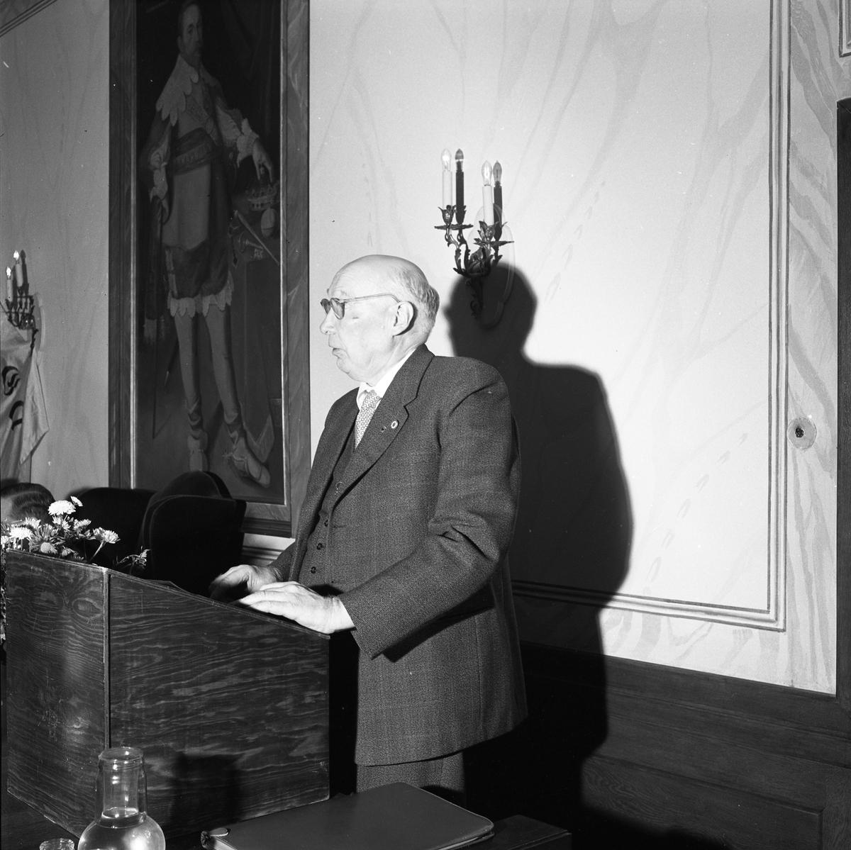 """Gustaf Johansson (""""Murar-Gustaf""""), från Hantverksföreningen, delar ut Mästarbrev på Rådhuset. Han står i talarstolen i kommunfullmäktigesalen."""