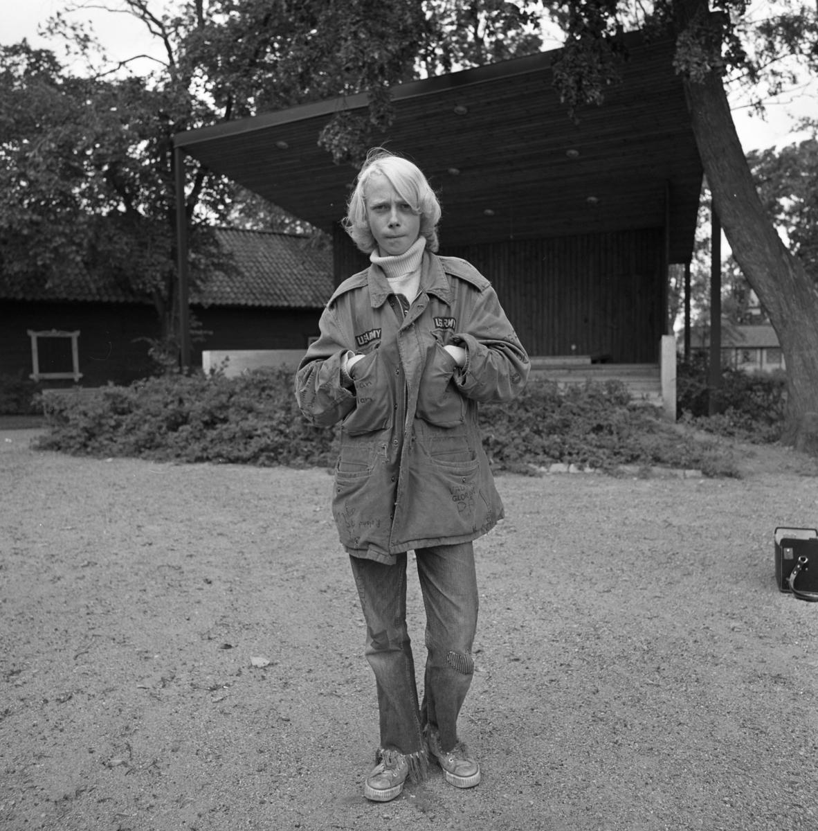 Greger Lindkvist i Ahllöfsparken / Olof Ahllöfs park Ung man, iklädd anorak och jeans, står framför scenen. Augusti 1965  Negativet finns i Reinhold Carlssons kartong 5_sida 25_neg 004.tif