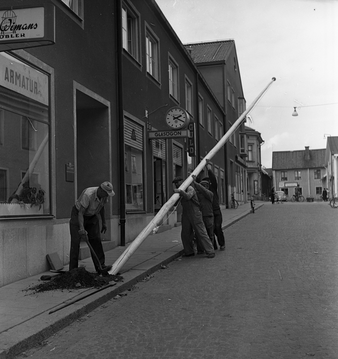 Här ordnas det inför konungens ankomst. Fyra män ska sätta upp en flaggstång. Kung Gustaf Vl Adolf ska komma på Eriksgata 12 september. Järntorgsgatan. Butikerna skyltar med armatur, glasögon och guld.