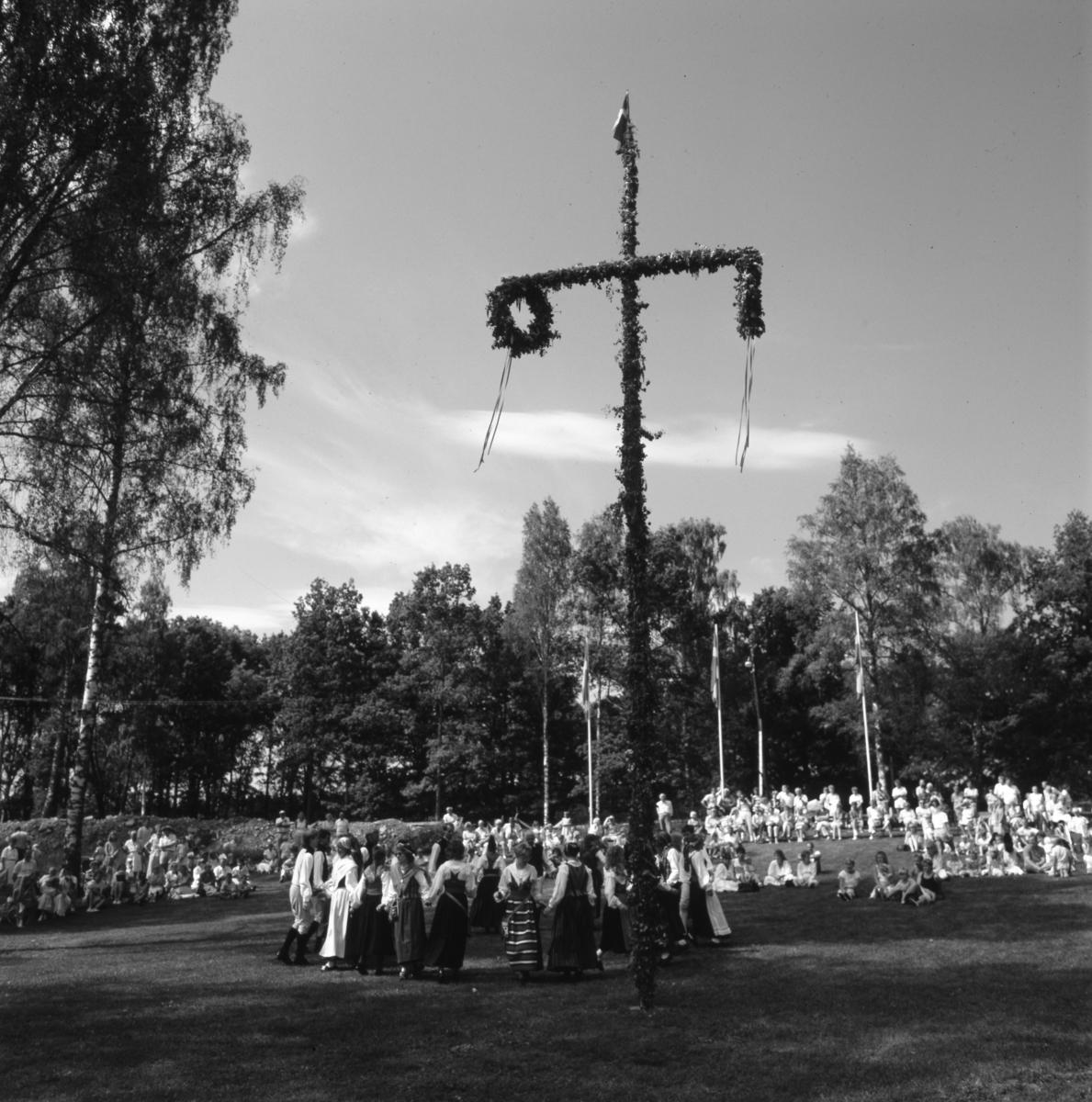 Midsommarfirande i Arboga Folkets park. Folkdanslaget uppträder för publiken. Midsommarstången är rest och flaggorna hissade.
