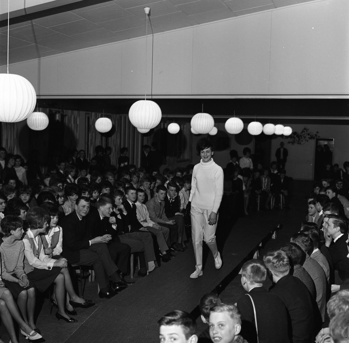 Ungdomsträff med modevisning. En ung kvinna visar polojumper och långbyxor. Ungdomarna sitter vid sidan och ser på.
