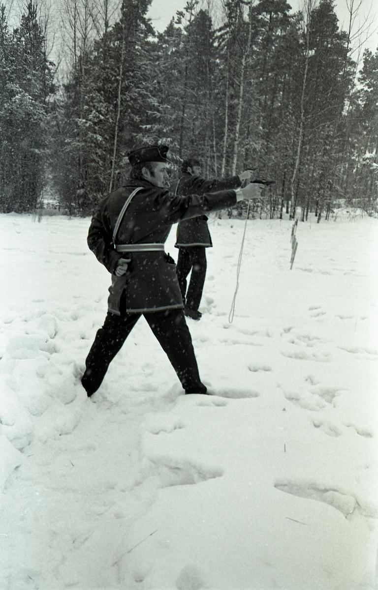 Polisen tränar pistolskytte. Två polismän, i uniform, skjuter med pistol. Det snöar. Skog i bakgrunden.