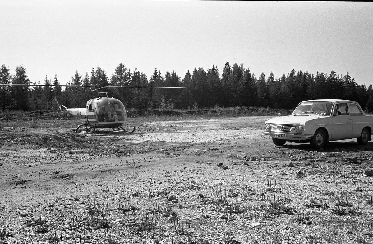 Polishelikopter vid Götes bilverkstad (bilverkstaden syns inte i bild). En bil står parkerad. Skog i bakgrunden.