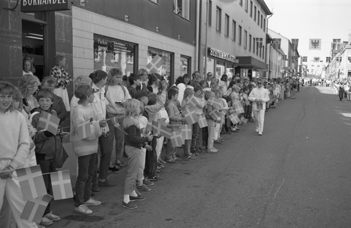 Allmänhet och skolbarn med flaggor i händerna är samlade på Nygatan. Närmast i bild ses Bokhandeln och Systembolaget. Riksdagsjubileet 1985. 550-årsminnet av Sveriges första riksdag firas i Arboga. Kungaparet och höga politiker gästar stan.