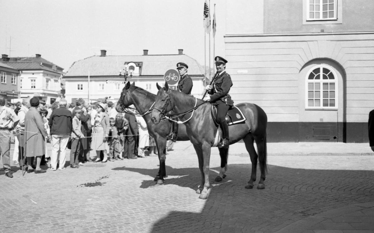 Riksdagen 550 år. Jubileet firas i Arboga. Två ridande poliser på Rådhusgatan. Publiken trängs bakom avspärrningen på Stora torget.