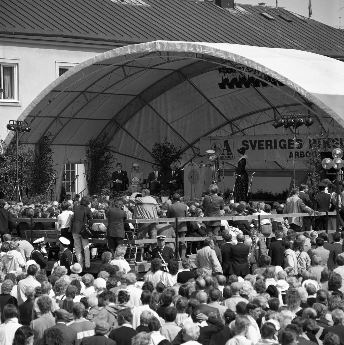 Sveriges riksdag 550 år firas i Arboga. En scen är uppbyggd vid rådhusgården. Där sitter statsminister Olof Palme, drottning Silvia, kung Carl XVl Gustaf och talman Ingemund Bengtsson. Med på scenen finns två medeltidsklädda personer. En stor publik har samlats på torget. Riksdagsjubileet 1985.