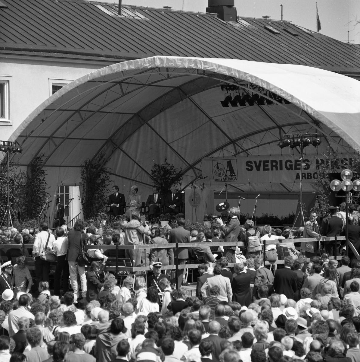I Arboga firas 550-årsminnet av Sveriges första riksdag.  En scen är uppbyggd vid Rådhusgården. Där sitter, från vänster, statsminister Olof Palme, drottning Silvia, Kung Carl XVl Gustaf och talman Ingemund Bengtsson. Fotografer och poliser syns bland publiken. Riksdagsjubileet.