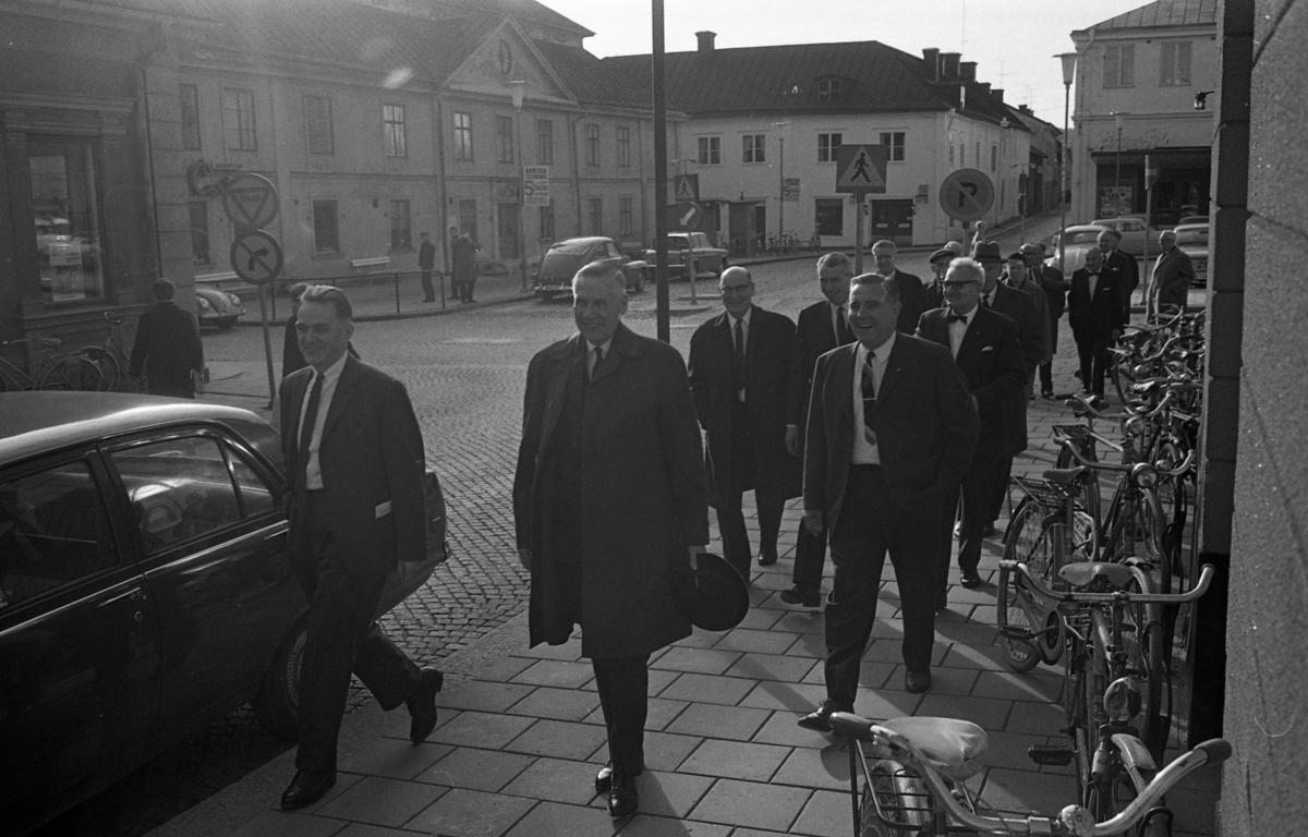 Statsutskottet besöker Arboga. Den glade mannen till höger är Nils Brodin. Bakom honom går Jonas Carlsson tillsammans med Gösta Bohman, som är utskottets ordförande (senare Moderatledare). I bakgrunden ses Stadsgården, infarten till Västerlånggatan, Sture-Bio och bilar på Stora torget. Efter rådhusväggen står många cyklar parkerade.