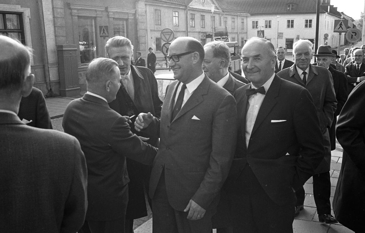Statsutskottet besöker Arboga. Politikerna är på väg in i rådhuset. Mannen som ler mot fotografen är Rune Hedlund från Sala (senare landstingsråd i Västmanland). Mannen med ryggen mot fotografen, och en cigarett i handen, är Gustav Danielsson. Han samspråkar med Olle Göransson. I bakgrunden ses Stadsgården och infarten till Västerlånggatan.