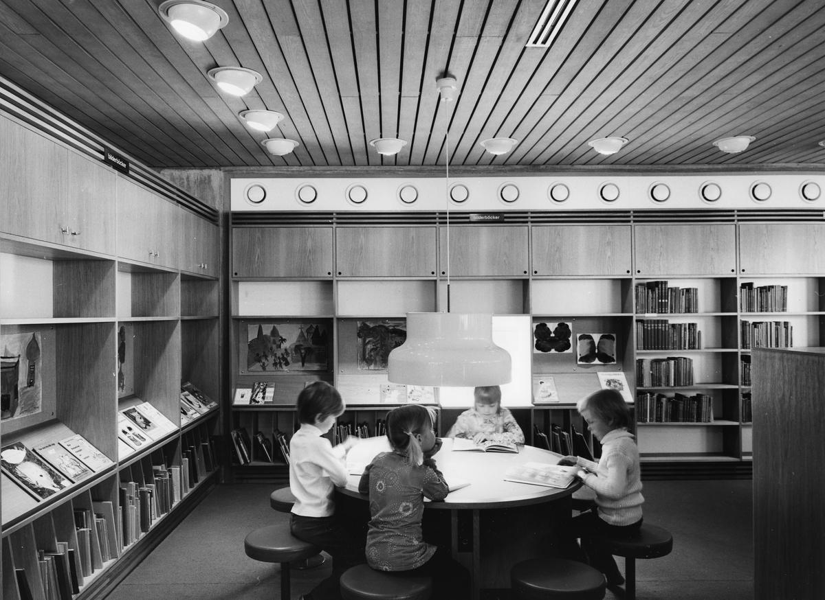 Arboga Stadsbibliotek, interiör. Barnavdelningen, belägen strax till höger när man kommer in genom entrén. Vid ett runt bord sitter fyra barn och läser. De sitter på läderklädda pallar med metallstativ. Rummet är inramat av bokhyllor med böcker på låg höjd.