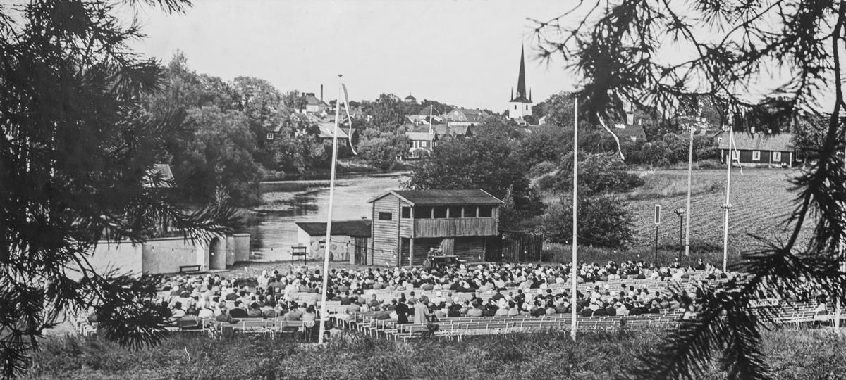 """Publik och den uppbyggda spelplatsen för Giv oss fred, intill Arbogaån. I bakgrunden ses tornet på Heliga Trefaldighetskyrkan. """"Giv oss fred"""", även kallat """"Arbogaspelet"""", är ett teaterstycke skrivet av Rune Lindström 1961. Handlingen, som är inspirerad av Arbogas klosterhistoria, är förlagt till början av 1500-talet. Uruppförandet skedde den 11 augusti 1962 och Rune Lindström spelade Engelbrekt Gertsson. Lions Club i Arboga stod för arrangemanget. Föreställningarna regnade bort och det blev ett stort ekonomiskt bakslag för föreningen. Spelet har framförts igen; 1987, 1988, 2012 och 2015 av medlemmar i """"Bygdespelets Vänner""""."""