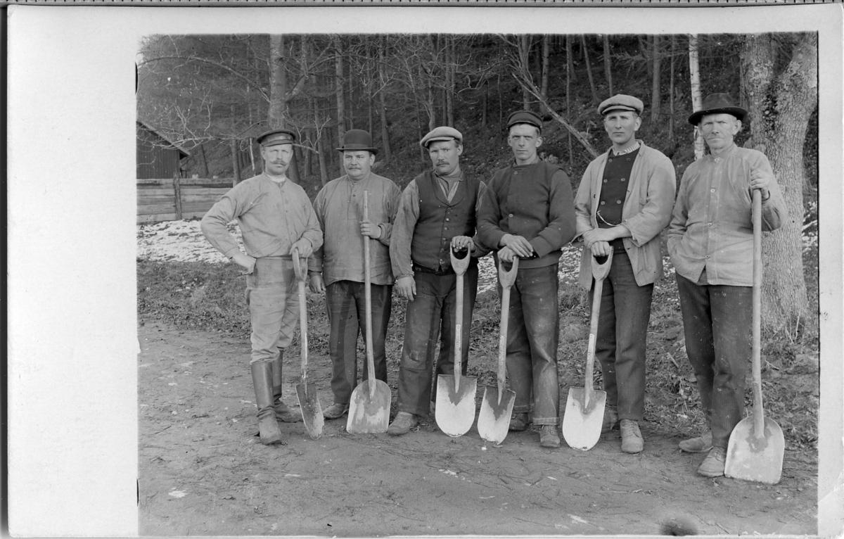 Arbetslaget på gamla vägen vid Arboga Möjligen nödhjälpsarbete? Sex män med spadar och skyfflar. Alla bär hatt eller annan huvudbonad.