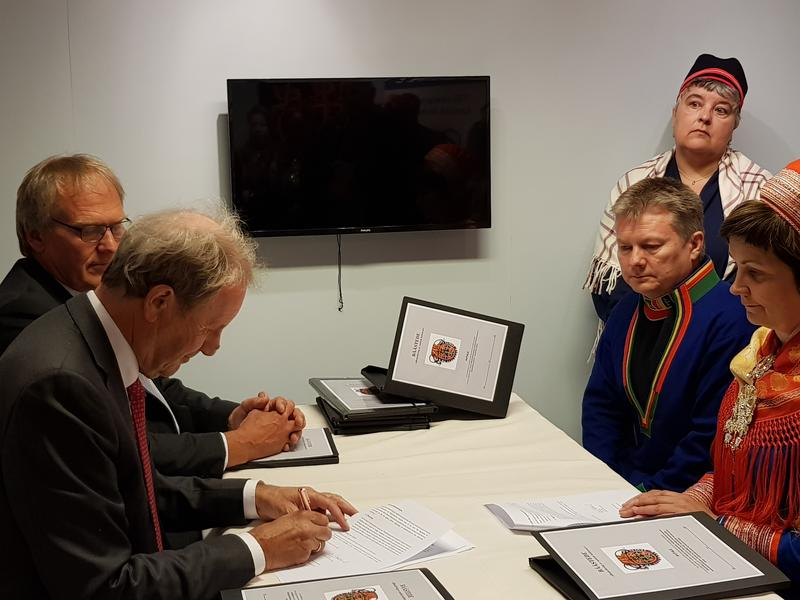 Olav Aaraas signerer avtalen med Karl Kalhovd,  Lars Magne Andreassen, Harieth Aira og sametingspresident Aili Keskitalo på Kautokeino Bygdetun.