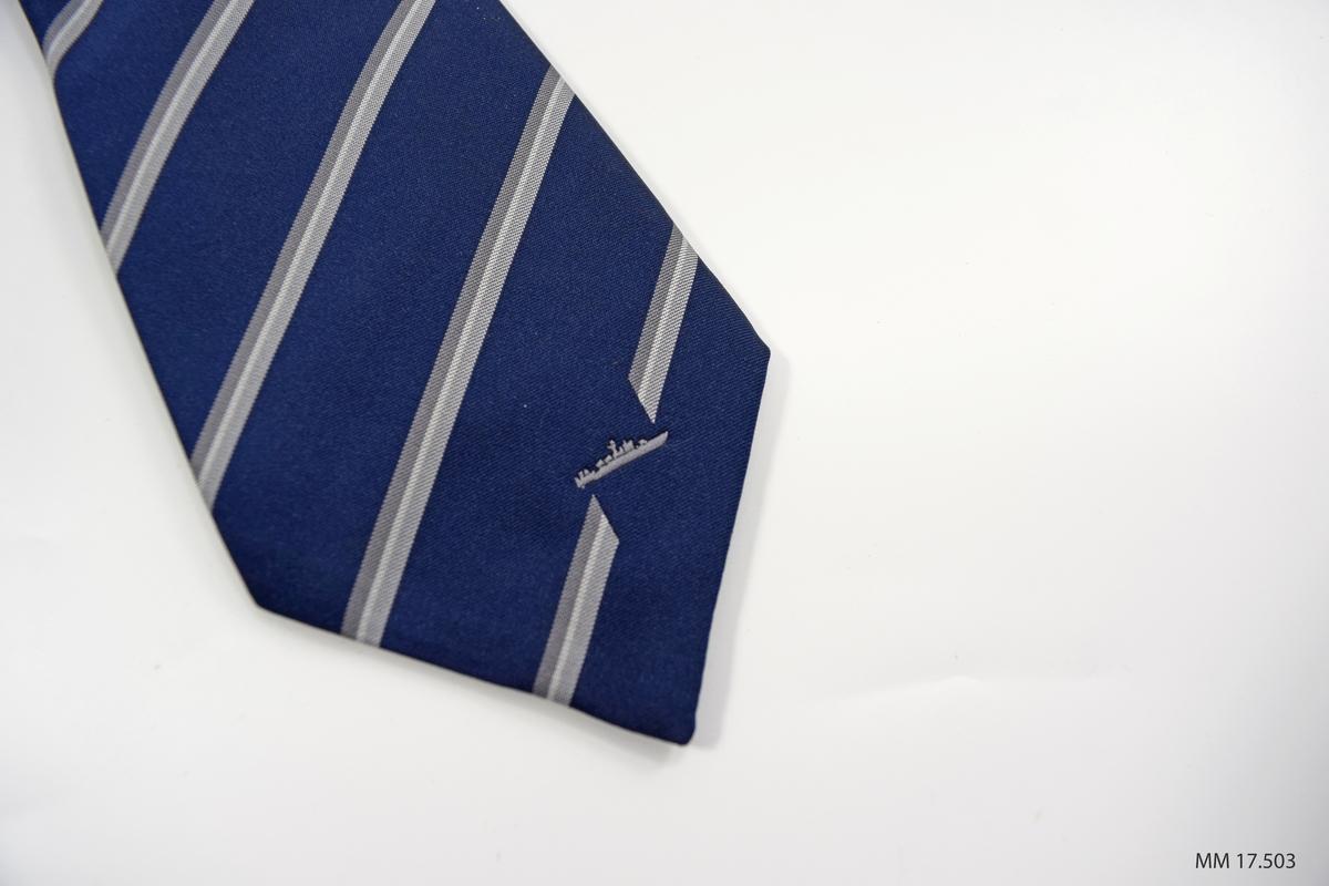 Marinblå slips med grå och vita diagonalt vävda ränder. Vid spetsen litet grått fartyg invävt, kustkorvett typ Stockholm. På baksidan fastsydd etikett med text i gult. Fodrad i blått.