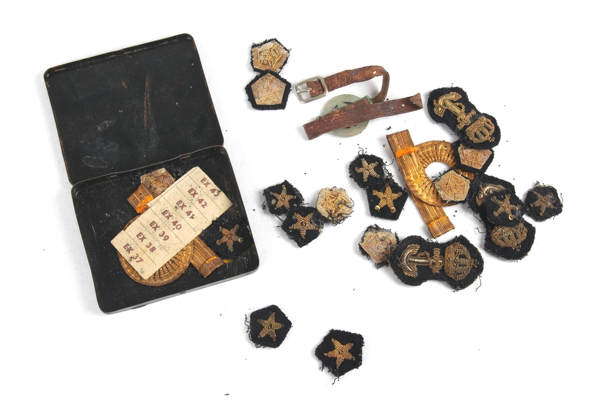 Metallboks opprinnelig for fargekritt, med jakkemerker, armbånd og del av et rasjoneringskort.