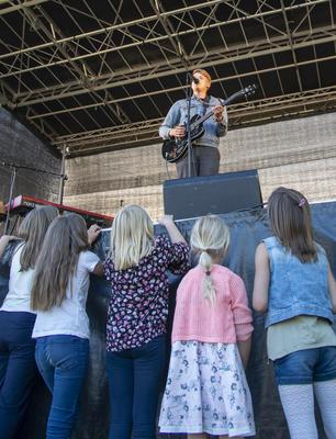 En ung gitarist i dongerijakke står på scenen, små jenter står foran og ser opp på ham.