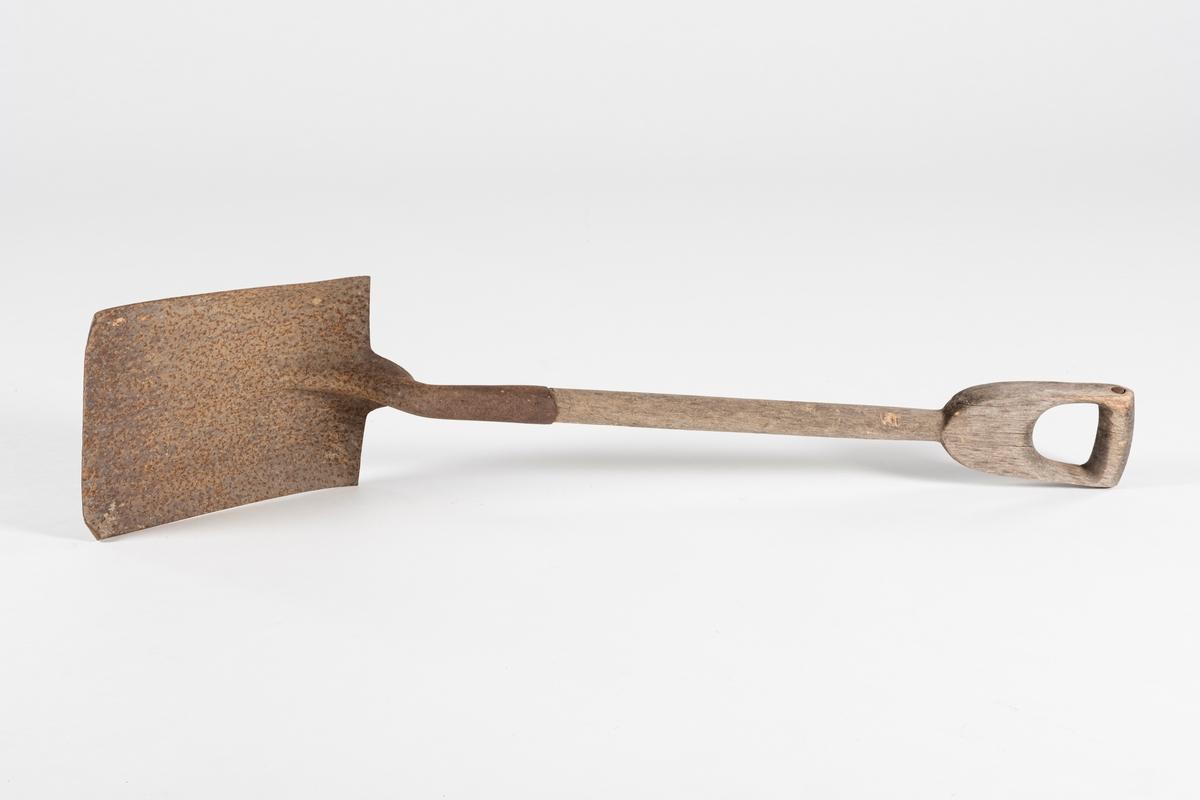 Spade med rektangulær form. Skaft i ett stykke med håndtak. Jernnagle som forsterkning gjennom øvre del av håndtaket. Spadehodet er naglet fast til skaftet.