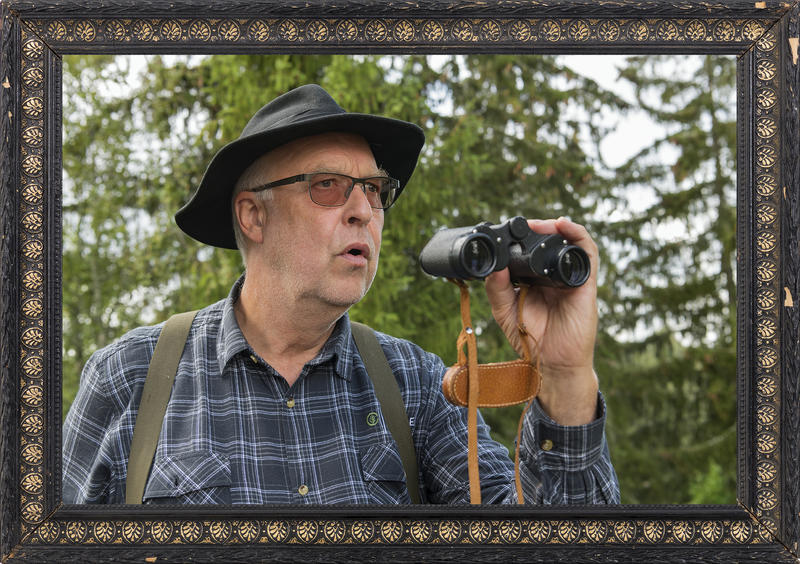 Skogvokter Tobias kikker skremt opp fra kikkerten etter å ha oppdaget et mulig branntilfelle i skogen. Foto: Bård Løken /Anno Norsk skogmuseum