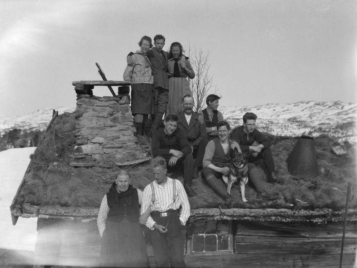 Folk foran hytte i fjellet.