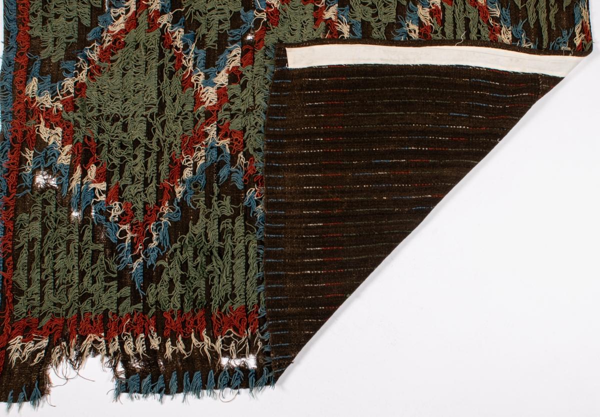 Rya, så kallad glesrya i två våder. Randig i rött, grönt, blått och vitt på en brun botten.