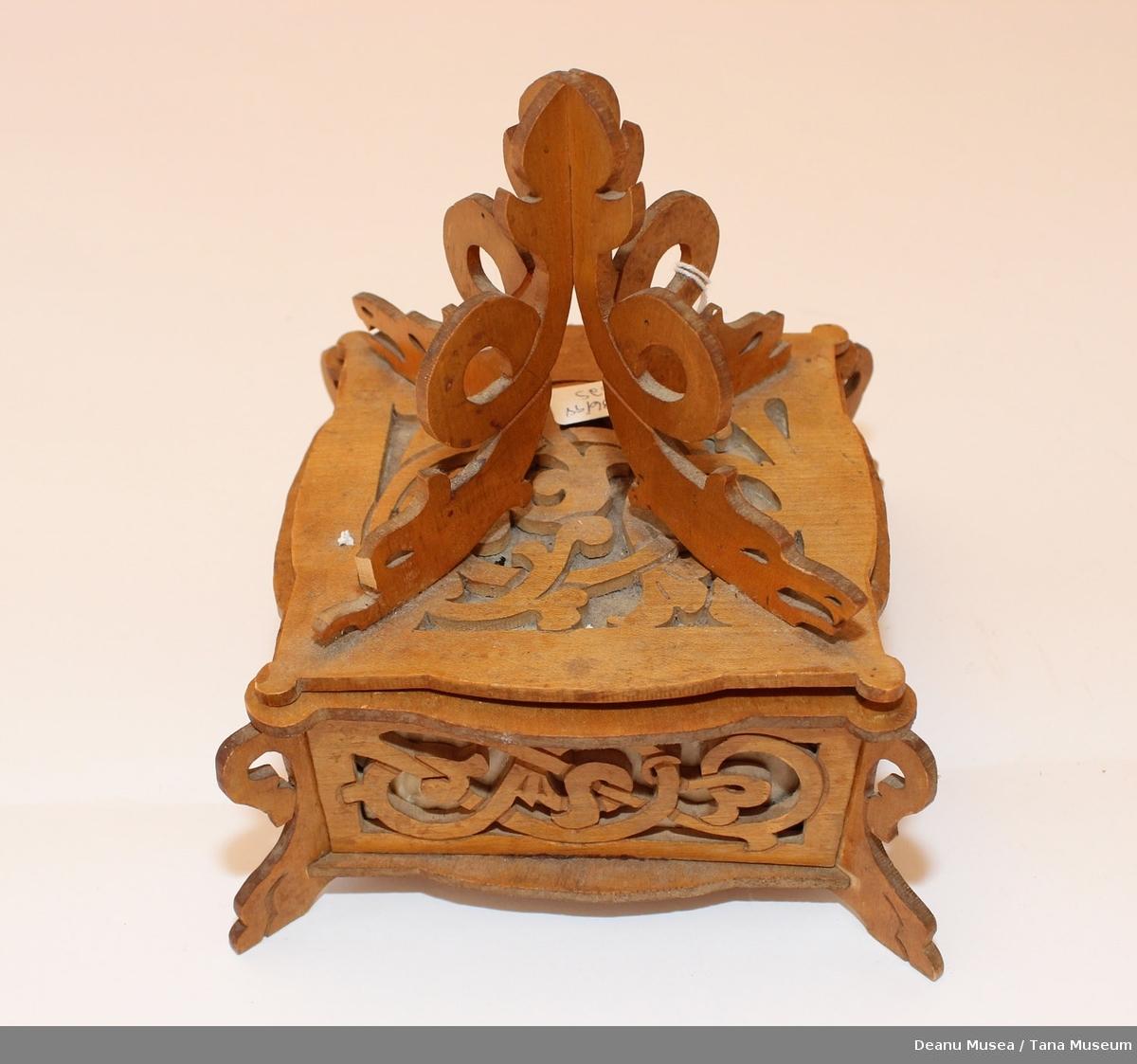 En smykkekiste i tre med puter i. 4 drageutskjæringer på toppen. Kanten har også utskjæringer.