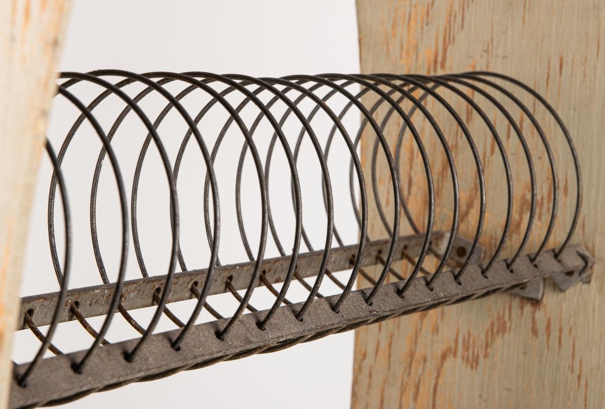 Torkställ med gavlar av gråmålad plywood och uppställningskonstruktion av galvaniserat stål.