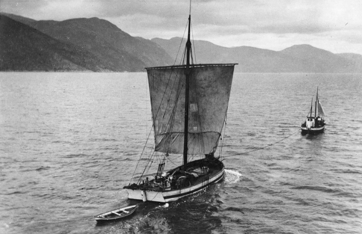 Sognejekten NORDSTJERNEN under slep av en motorgående fiskeskøyte i fjordlandskap, lettbåt på slep bak jekten. Jekten skal ha vært den siste råseilrigga  sognejekten.