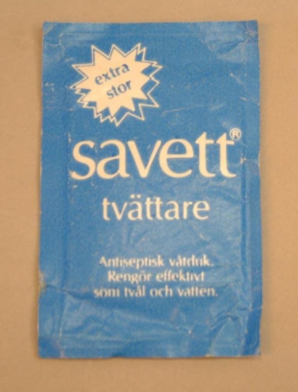 """Våtservett av märket Savett i förpackning av blått papper. Artikelnummer 6565610. Vit i mitten med blå SJ-logga. Andra sidan är blå . Text i vitt """"Savett"""" Antiseptisk våtduk. Rengör effektivt som tvål och vatten."""