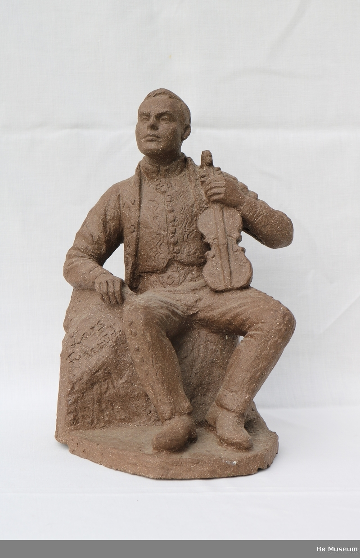 Statuen forestiller felespelaren Lars Fykerud sittande i folkedrakt mens han holder fela i venstre arm.
