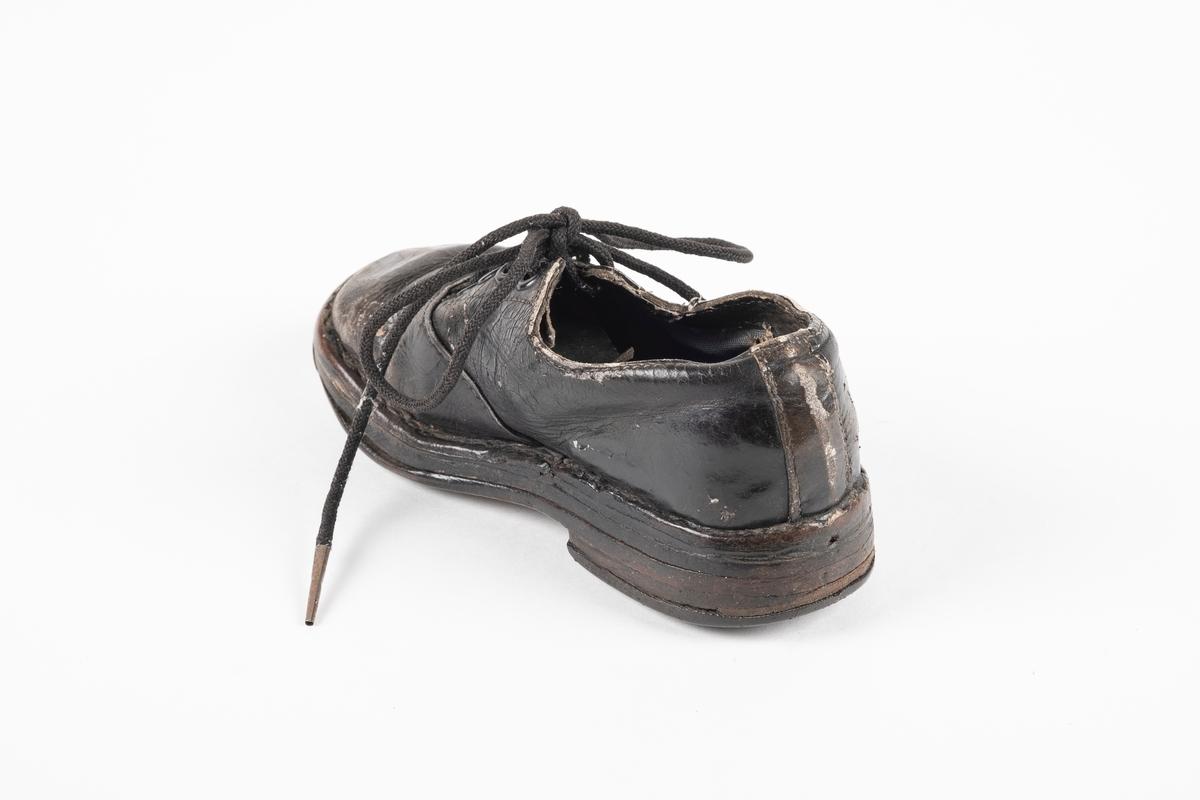 Et randsydd barnesko (høyre sko) av lær. Skoen har snøring med runde lisser. Maljene er av metall. Sålen er av lær og er forsterket med spiker på hælen og ved tuppen på undersiden.