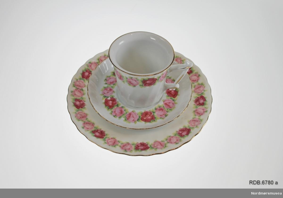 """Kaffeservise bestående av 7 par kaffekopper med tefat og asjetter. Serviset er i hvitt porselen med et """"bølgemønster"""" i selve porselenet. Dekor i form av en bord av røde og rosa roser og grønne blader rundt alle deler. Gullkanter. Tilnærmet sylinderformet kopp, litt videre øverst enn nederst med """"piket"""" håndtak."""