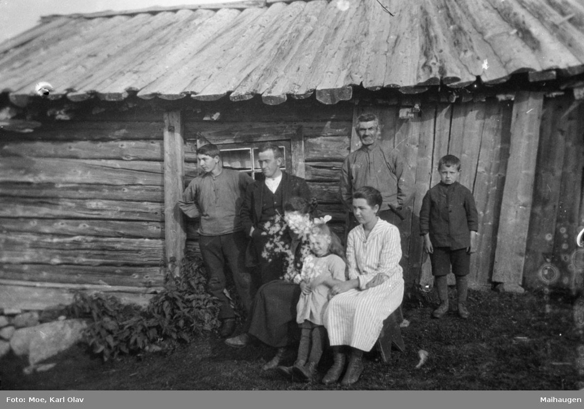 Fem voksne og to barn foran et seterhus eller ei hytte